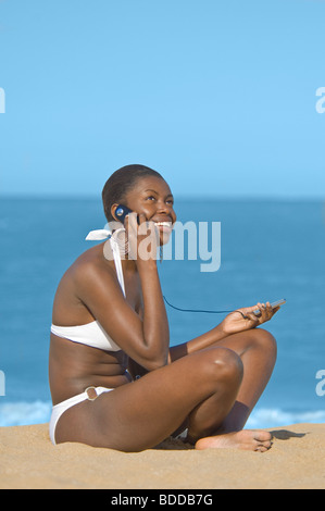 A slim attractive young African woman making a call on her mobile phone on a beach with a blue sea and sky in the - Stock Photo