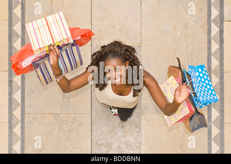 An aerial view of a slim attractive trendy young African woman at a shopping center very happy on a shopping spree. - Stock Photo