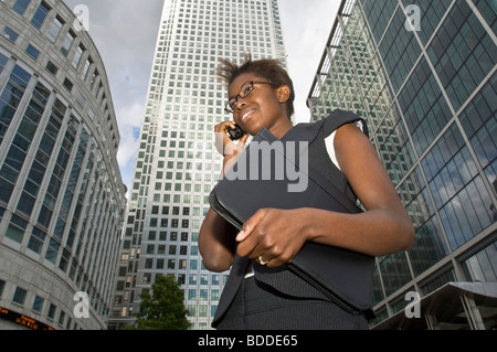 An attractive African business woman talking on her mobile phone at Canary Wharf with modern office buildings in - Stock Photo
