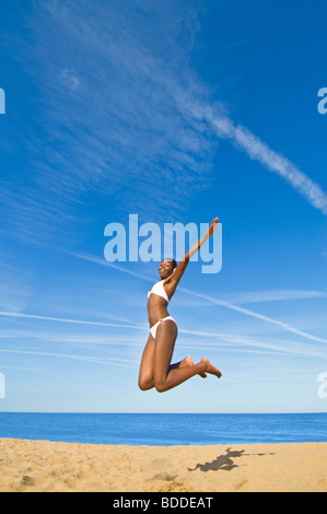 Close focus wide angle of a slim attractive African woman jumping on a sandy beach with a blue sea and sky in the - Stock Photo