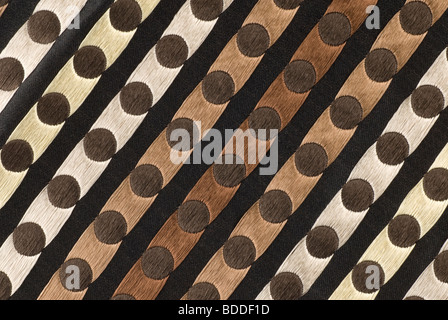 woven textile forming parallel diagonal stripes and rows of circles resembling an abstract design colours cream - Stock Photo