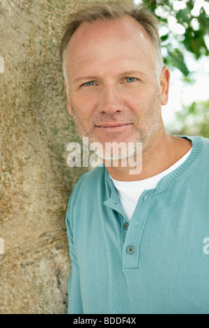 Man leaning against a tree trunk - Stock Photo