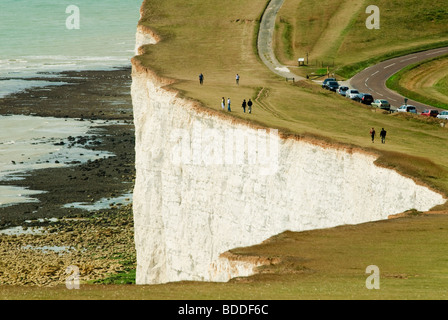 People walking near the edge of the white chalk cliffs at Beachy Head Eastbourne England looking out over the English - Stock Photo