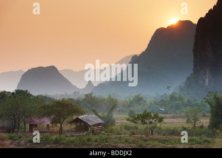 the sun dissappearing over the mountains nr Vang Vieng, Laos - Stock Photo