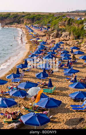 beach holiday. Holidaymakers sunbathing on a crowded Ammes Beach on the Greek Mediterranean island of Kefalonia - Stock Photo