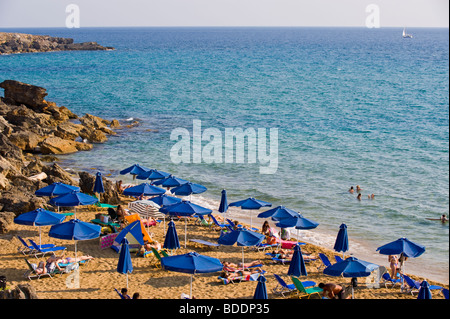 Holidaymakers sunbathing on a crowded Ammes Beach on the Greek Mediterranean island of Kefalonia Greece GR - Stock Photo