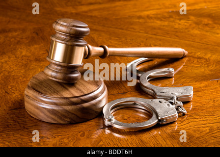 A gavel and block on a rich, cherry desktop with handcuffs. - Stock Photo
