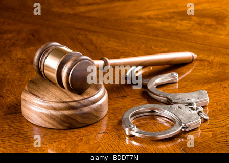 A gavel and block on a richly colored cherry wooden desk with handcuffs. - Stock Photo