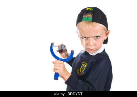 A young blond haired caucasian 5 year old boy about to fire a catapult wearing a back to front baseball cap.  He - Stock Photo