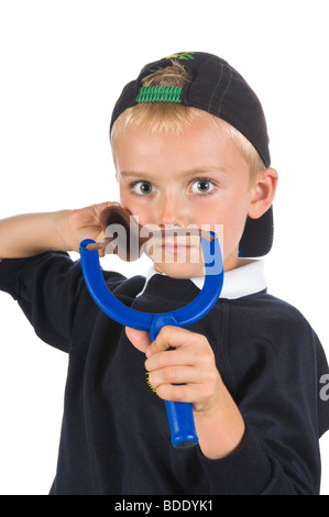 A cheeky young blond haired caucasian 5 year old boy holding his catapult wearing a back to front baseball cap. - Stock Photo