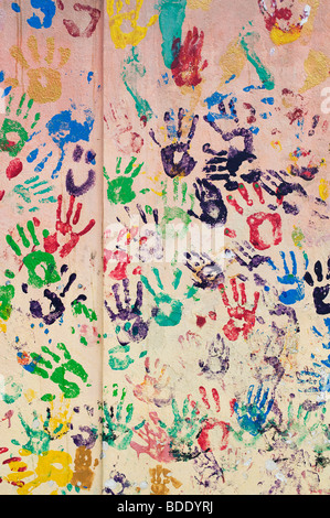 Kids painting with hand prints on a wall on the Cowley Road in Oxford - Stock Photo