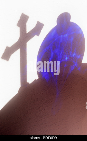 Shadow on white wall of circular table with free-standing crucifix and round blue glass vase - Stock Photo