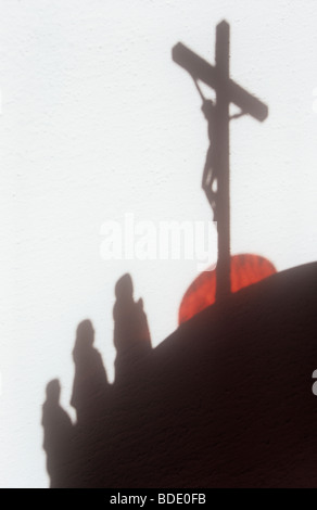 Shadow on white wall of Jesus Christ on crucifix with three robed figures standing on slope below and red setting - Stock Photo