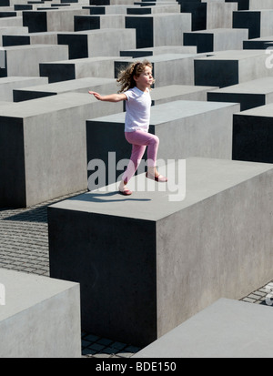 young girl posing on top of concrete blocks at the Memorial to the Murdered Jews of Europe in central Berlin Germany - Stock Photo