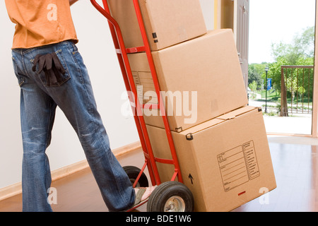 Boxes stacked on cart in empty condo. - Stock Photo