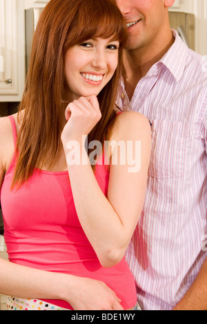 Man woman standing together in the kitchen. - Stock Photo