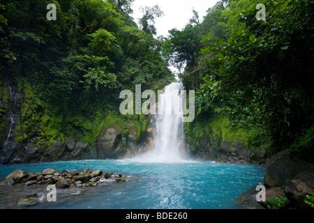Rain forest waterfall along the vibrant blue Rio Celeste river in Tenorio Volcano National Park, Costa Rica. - Stock Photo