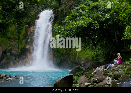 Female hiker resting beneath a waterfall along the vibrant blue Rio Celeste river in Tenorio Volcano National Park, - Stock Photo