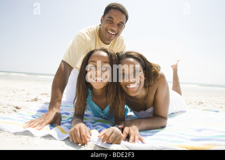 Father and Mother playing on the beach with family - Stock Photo