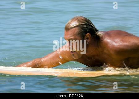 Man paddling on surfboard - Stock Photo