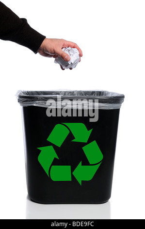 Man's hand placing paper in trash can with recycle symbol - Stock Photo