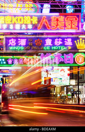 Neon signs and bus light trail in Tsim Sha Tsui, Kowloon, Hong Kong, China. - Stock Photo