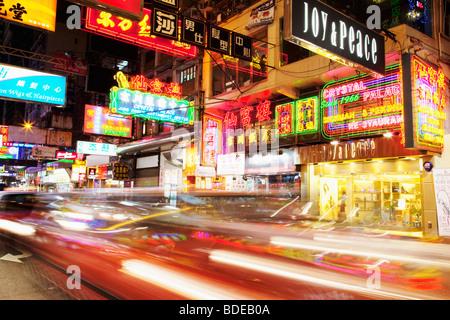 Neon signs and car light trail in Tsim Sha Tsui, Kowloon, Hong Kong, China. - Stock Photo