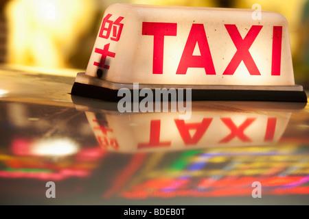 Neon signs and taxi light Tsim Sha Tsui Kowloon Hong Kong China - Stock Photo