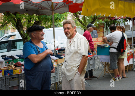 Two friends talking at a market in Najac, France. - Stock Photo
