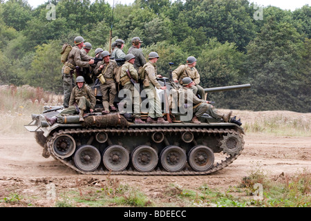 A Group Of Re-enactor In American Second World Uniforms Riding On A Chaffee Tank - Stock Photo