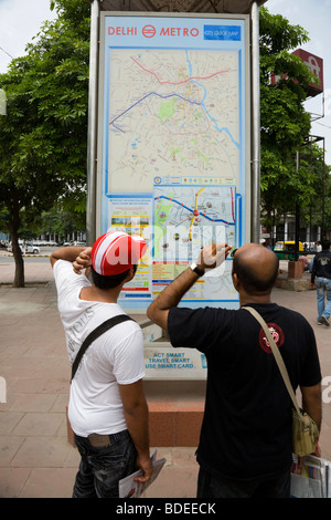 Two Indian men look at an information route map of the Delhi Metro system on display outside Rajiv Chowk station. - Stock Photo