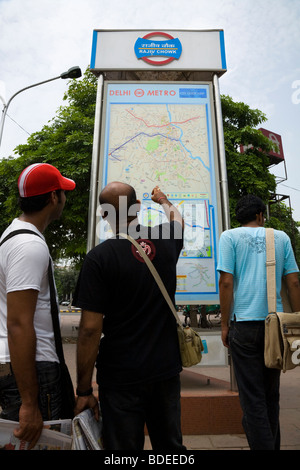 Indian men look at an information route map of the Delhi Metro system on display outside Rajiv Chowk station. Delhi, - Stock Photo