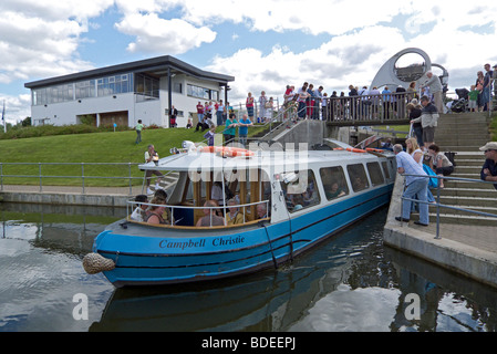 Canal Boat Campbell Cristie leaving the Falkirk Wheel canal basin through the lock to enter the Forth and Clyde - Stock Photo