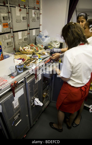 Members of cabin crew prepare to serve meals in the galley of a Virgin Atlantic aircraft during Mumbai to London - Stock Photo