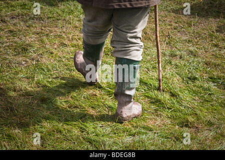 Detail of countryman in green wellington boots carrying a walking stick - Stock Photo
