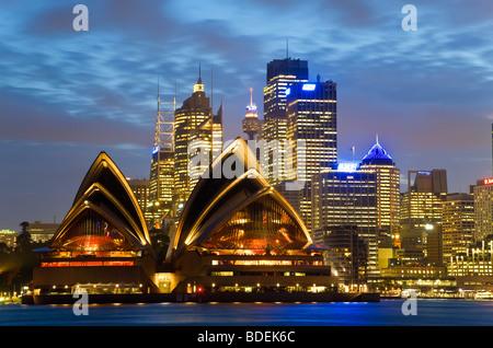 Australia, Sydney, View across Sydney harbour to Sydney Opera House & skyline at dusk - Stock Photo