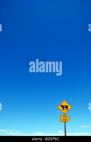Yellow 'Open Range' traffic sign with bullet holes against clear blue sky.