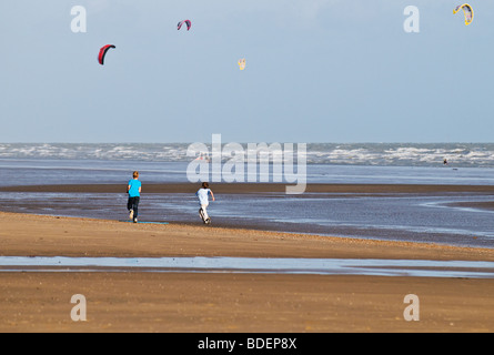 Two young boys running along the beach at Camber sands in Sussex.  Photo by Gordon Scammell - Stock Photo