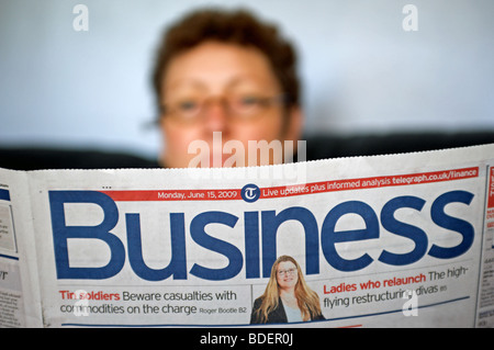 Woman reading the Daily Telegraph Business section - Stock Photo