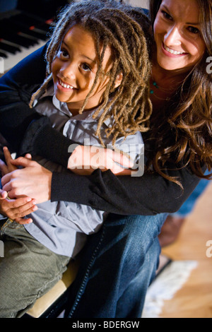 Mother and mixed-race son sitting on couch in living room - Stock Photo