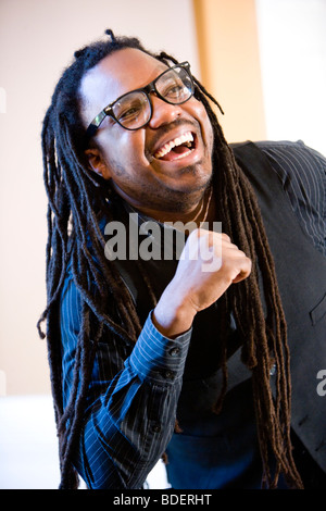 Portrait of Jamaican man with dreadlocks laughing - Stock Photo