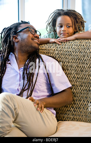 Jamaican father and young son with dreadlocks on sunroom on sofa - Stock Photo
