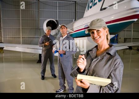 Three airplane mechanics standing next to small planes in hangar - Stock Photo