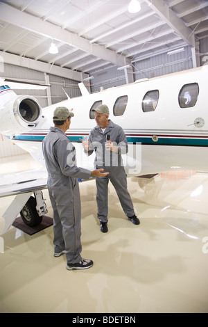 Two airplane mechanics having argument in hangar next to private jet - Stock Photo