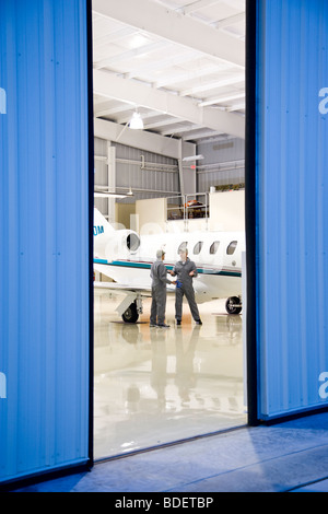 Two airplane mechanics having discussion in hangar next to private jet - Stock Photo