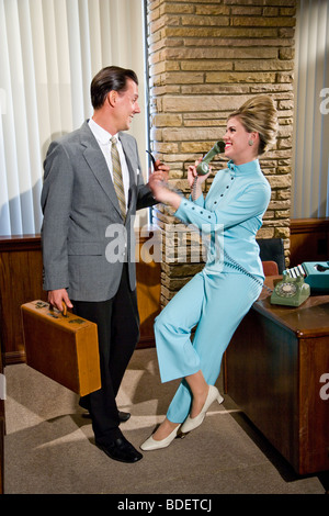 Vintage portrait of businessman and secretary holding hands in office - Stock Photo