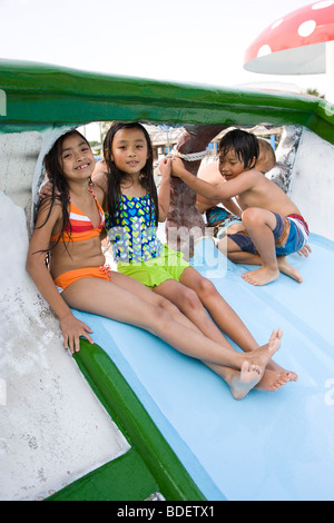 Multi-ethnic children on waterslide at water park - Stock Photo