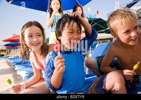 Multi-ethnic children at water park in summer eating popsicles - Stock Photo