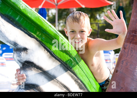 Young blonde boy waving at water park in summer - Stock Photo