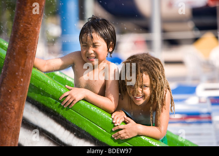 Two boys at water park in summer playing on slide near pool - Stock Photo